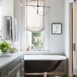 Mid-sized eclectic master medium tone wood floor and beige floor claw-foot bathtub photo in New York with furniture-like cabinets, gray cabinets, a two-piece toilet, white walls, an undermount sink and marble countertops
