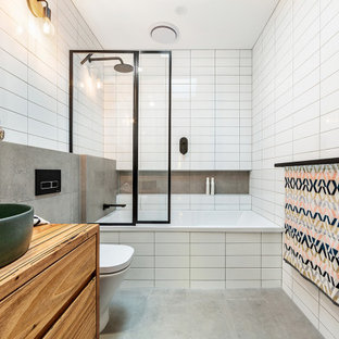 Design ideas for a small contemporary master bathroom in Melbourne with flat-panel cabinets, medium wood cabinets, a drop-in tub, white tile, a vessel sink, wood benchtops, grey floor and brown benchtops.