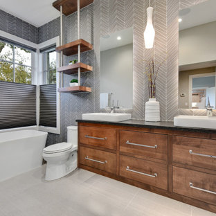 Trendy gray tile gray floor and double-sink freestanding bathtub photo in Austin with flat-panel cabinets, dark wood cabinets, a vessel sink and black countertops