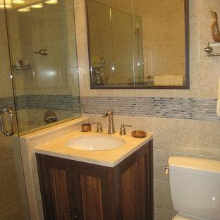 Modelo de cuarto de baño principal, asiático, de tamaño medio, con puertas de armario de madera oscura, ducha empotrada, sanitario de dos piezas, baldosas y/o azulejos beige, azulejos en listel, paredes beige, suelo de mármol, lavabo bajoencimera y encimera de mármol
