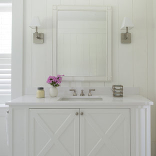 Inspiration for a large coastal linoleum floor and white floor bathroom remodel in San Francisco with white cabinets, white walls, white countertops, furniture-like cabinets and an undermount sink