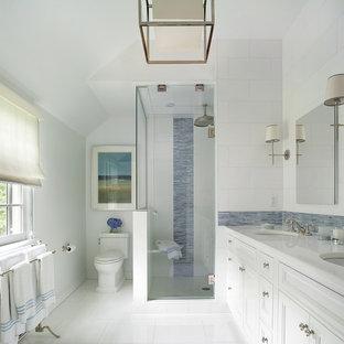 Foto på ett stort vintage vit en-suite badrum, med ett undermonterad handfat, luckor med infälld panel, vita skåp, en dusch i en alkov, en toalettstol med separat cisternkåpa, blå kakel, stickkakel, marmorbänkskiva, vita väggar och klinkergolv i keramik