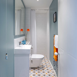 Design ideas for a small contemporary shower room in Hampshire with flat-panel cabinets, white cabinets, a walk-in shower, a wall mounted toilet, multi-coloured tiles, ceramic tiles, blue walls, ceramic flooring, a wall-mounted sink and tiled worktops.