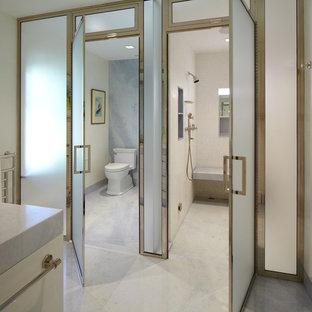 Geräumiges Klassisches Badezimmer En Suite mit flächenbündigen Schrankfronten, weißen Schränken, Duschnische, weißer Wandfarbe, Marmor-Waschbecken/Waschtisch, Wandtoilette mit Spülkasten, weißen Fliesen, Marmorboden, Steinplatten, Falttür-Duschabtrennung, grauem Boden und WC-Raum in New York