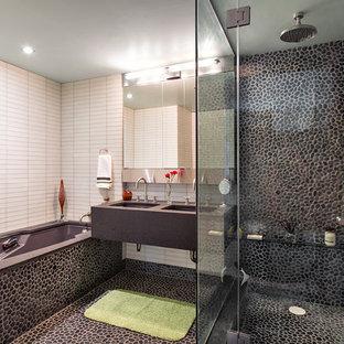 Immagine di una stanza da bagno padronale minimal di medie dimensioni con lavabo sottopiano, vasca sottopiano, piastrelle grigie, piastrelle di ciottoli, pavimento con piastrelle di ciottoli, nessun'anta, ante grigie, top in cemento, doccia ad angolo, WC monopezzo e pareti beige