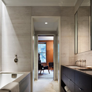 Inspiration for a modern ensuite bathroom in New York with flat-panel cabinets, brown cabinets, an alcove bath, grey tiles, grey walls, a submerged sink and beige floors.