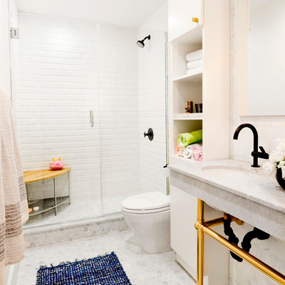 Example of a mid-sized transitional 3/4 white tile and subway tile mosaic tile floor alcove shower design in New York with open cabinets, white cabinets, white walls, an undermount sink, a one-piece toilet, marble countertops, a hinged shower door and gray countertops