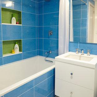 Diseño de cuarto de baño infantil, moderno, pequeño, con lavabo bajoencimera, armarios con paneles lisos, puertas de armario blancas, encimera de mármol, bañera empotrada, sanitario de una pieza, baldosas y/o azulejos azules, baldosas y/o azulejos de porcelana, paredes azules y suelo de baldosas de porcelana