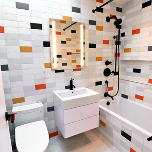 Example of a mid-sized minimalist kids' red tile and ceramic tile marble floor and beige floor drop-in bathtub design in New York with flat-panel cabinets, white cabinets, a two-piece toilet, white walls, a pedestal sink, quartzite countertops and white countertops