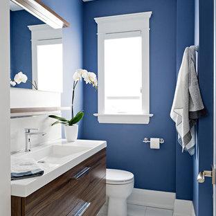 Imagen de cuarto de baño principal, moderno, pequeño, con armarios con paneles lisos, puertas de armario de madera en tonos medios, bañera empotrada, ducha empotrada, sanitario de dos piezas, baldosas y/o azulejos de cemento, paredes azules, lavabo integrado, encimera de acrílico, suelo blanco, ducha con cortina, encimeras blancas y suelo de baldosas de cerámica