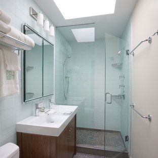 Contemporary bathroom in New York with a trough sink, dark wood cabinets, a double shower, a two-piece toilet, blue tile, glass tile and flat-panel cabinets.