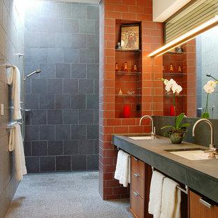 Diseño de cuarto de baño actual con lavabo bajoencimera, armarios con paneles lisos, puertas de armario de madera oscura, baldosas y/o azulejos naranja, ducha a ras de suelo y suelo gris