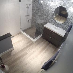 Ejemplo de cuarto de baño principal, actual, pequeño, con ducha esquinera, sanitario de una pieza, baldosas y/o azulejos azules, paredes blancas, suelo de madera en tonos medios, lavabo integrado y armarios con paneles lisos