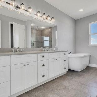 Imagen de cuarto de baño principal, de estilo de casa de campo, grande, con armarios estilo shaker, puertas de armario blancas, bañera exenta, ducha abierta, sanitario de una pieza, baldosas y/o azulejos grises, baldosas y/o azulejos con efecto espejo, paredes grises, suelo de baldosas de porcelana, lavabo bajoencimera, encimera de cuarzo compacto, suelo gris, ducha abierta y encimeras grises