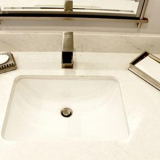 Стильный дизайн: главная ванная комната среднего размера в стиле современная классика с плоскими фасадами, белыми фасадами, отдельно стоящей ванной, угловым душем, керамогранитной плиткой, серыми стенами, полом из ламината, врезной раковиной, столешницей из искусственного кварца, коричневым полом и душем с распашными дверями - последний тренд