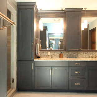 Example of a large transitional master multicolored tile and glass sheet limestone floor and gray floor alcove shower design in Other with recessed-panel cabinets, gray cabinets, a two-piece toilet, gray walls, an undermount sink, engineered quartz countertops, a hinged shower door and beige countertops