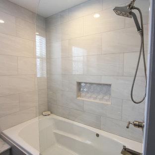 クリーブランドの小さいトランジショナルスタイルのおしゃれなマスターバスルーム (レイズドパネル扉のキャビネット、グレーのキャビネット、アルコーブ型浴槽、アルコーブ型シャワー、分離型トイレ、グレーのタイル、磁器タイル、グレーの壁、磁器タイルの床、アンダーカウンター洗面器、人工大理石カウンター、グレーの床、開き戸のシャワー) の写真