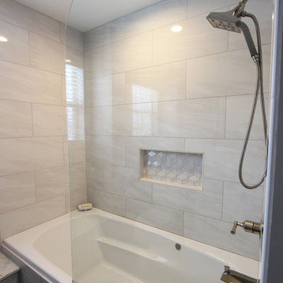 Bathroom - small transitional master gray tile and porcelain tile porcelain tile and gray floor bathroom idea in Cleveland with raised-panel cabinets, gray cabinets, a two-piece toilet, gray walls, an undermount sink, solid surface countertops and a hinged shower door