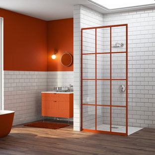 Photo of a large bohemian bathroom in Miami with flat-panel cabinets, orange cabinets, a freestanding bath, white tiles, orange walls, dark hardwood flooring, marble worktops, an open shower, metro tiles, a wall-mounted sink and white floors.