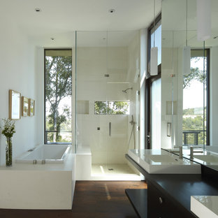 Стильный дизайн: главная ванная комната среднего размера в современном стиле с настольной раковиной, плоскими фасадами, темными деревянными фасадами, накладной ванной, угловым душем, бежевой плиткой, темным паркетным полом, столешницей из дерева, каменной плиткой, белыми стенами и черной столешницей - последний тренд
