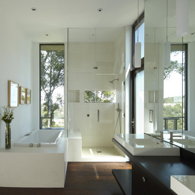 Mid-sized trendy master beige tile and stone tile dark wood floor bathroom photo in Los Angeles with a vessel sink, flat-panel cabinets, dark wood cabinets, wood countertops, white walls and black countertops
