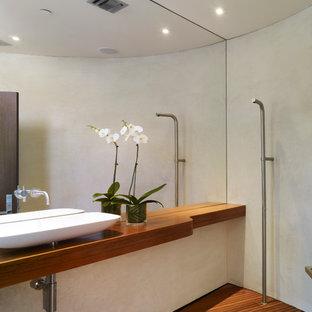 Inspiration pour une salle d'eau minimaliste de taille moyenne avec une vasque, une douche ouverte, un plan de toilette en bois, un mur blanc, béton au sol et un plan de toilette marron.
