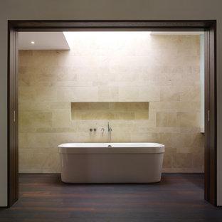 Foto di una stanza da bagno moderna di medie dimensioni con vasca freestanding, lavabo integrato, ante lisce, ante in legno bruno, WC monopezzo, piastrelle beige, pareti bianche, parquet scuro e piastrelle di pietra calcarea