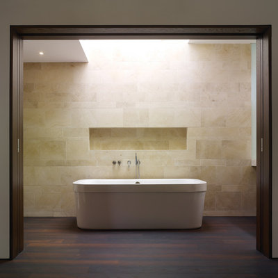 Freestanding bathtub - mid-sized modern beige tile and limestone tile dark wood floor freestanding bathtub idea in Los Angeles with an integrated sink, flat-panel cabinets, dark wood cabinets, a one-piece toilet and white walls