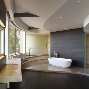 This is an example of a medium sized contemporary ensuite bathroom in Los Angeles with concrete worktops, a freestanding bath, an integrated sink, flat-panel cabinets, dark wood cabinets, a walk-in shower, beige tiles, stone tiles, white walls, dark hardwood flooring and an open shower.