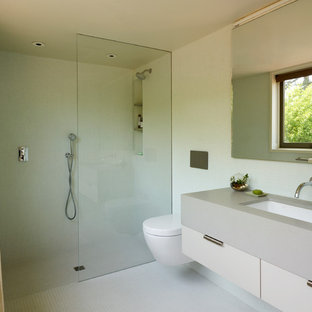 Mid-sized 1960s master green tile ceramic floor and yellow floor bathroom photo in San Francisco with flat-panel cabinets, gray cabinets, a wall-mount toilet, green walls and an integrated sink