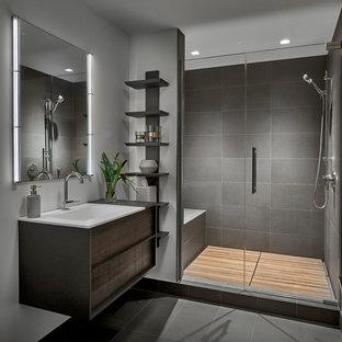 Ejemplo de cuarto de baño actual con armarios con paneles lisos, puertas de armario de madera en tonos medios, ducha empotrada, baldosas y/o azulejos grises, paredes grises, lavabo integrado, suelo gris y ducha con puerta con bisagras