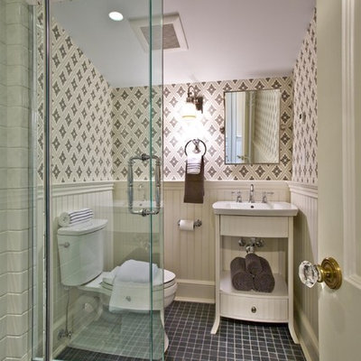 Corner shower - traditional black tile corner shower idea in New York with a wall-mount sink, furniture-like cabinets, white cabinets and a two-piece toilet