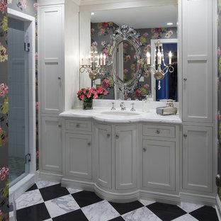Foto på ett vintage badrum, med ett undermonterad handfat, luckor med infälld panel, vita skåp, en dusch i en alkov, vit kakel och flerfärgat golv
