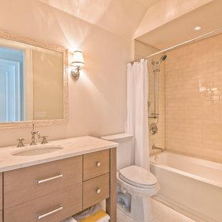 Klassisk inredning av ett mellanstort badrum, med släta luckor, skåp i mellenmörkt trä, ett badkar i en alkov, en dusch/badkar-kombination, en toalettstol med separat cisternkåpa, beige kakel, glaskakel, beige väggar, mosaikgolv, ett undermonterad handfat och marmorbänkskiva
