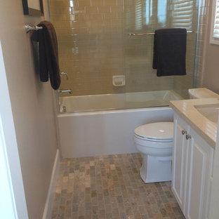 Idéer för ett litet klassiskt badrum, med luckor med upphöjd panel, vita skåp, ett badkar i en alkov, en dusch/badkar-kombination, en toalettstol med separat cisternkåpa, beige kakel, tunnelbanekakel, beige väggar, tegelgolv, ett undermonterad handfat, bänkskiva i akrylsten, flerfärgat golv och dusch med skjutdörr