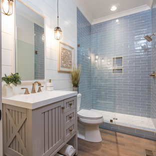 Ispirazione per una stanza da bagno country di medie dimensioni con piastrelle blu, piastrelle di vetro, pareti beige, pavimento in legno massello medio e porta doccia a battente