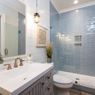 Idee per una stanza da bagno country di medie dimensioni con consolle stile comò, ante grigie, WC a due pezzi, piastrelle blu, piastrelle di vetro, pareti beige, pavimento in legno massello medio, lavabo sottopiano, pavimento marrone, porta doccia a battente e top bianco