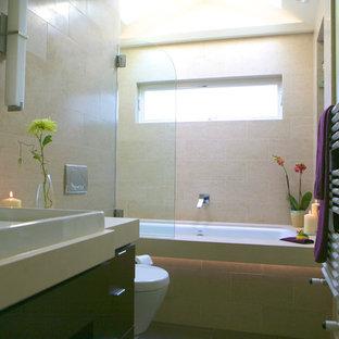 Foto de cuarto de baño minimalista con lavabo sobreencimera, armarios con paneles lisos, puertas de armario de madera oscura, encimera de cuarzo compacto, bañera encastrada, combinación de ducha y bañera, sanitario de pared, baldosas y/o azulejos beige y baldosas y/o azulejos de porcelana
