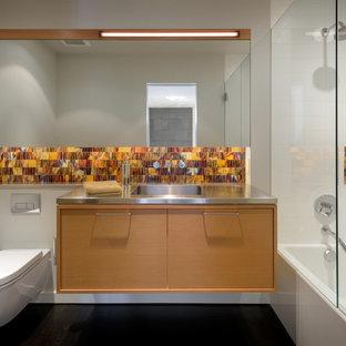 Неиссякаемый источник вдохновения для домашнего уюта: главная ванная комната среднего размера в современном стиле с фасадами островного типа, фасадами цвета дерева среднего тона, ванной в нише, душем над ванной, инсталляцией, оранжевой плиткой, стеклянной плиткой, белыми стенами, темным паркетным полом, монолитной раковиной, столешницей из нержавеющей стали, черным полом и душем с распашными дверями