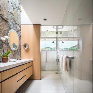 Diseño de cuarto de baño principal, actual, grande, con lavabo integrado, ducha a ras de suelo, armarios con paneles lisos, puertas de armario de madera clara, encimera de mármol, baldosas y/o azulejos blancos, baldosas y/o azulejos de vidrio, suelo de baldosas de cerámica, paredes blancas y suelo blanco