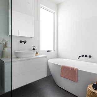 Design ideas for a mid-sized modern master bathroom in Melbourne with flat-panel cabinets, white cabinets, a freestanding tub, a corner shower, a one-piece toilet, white tile, ceramic tile, white walls, ceramic floors, a console sink, engineered quartz benchtops, black floor, a hinged shower door, white benchtops, a single vanity and a floating vanity.