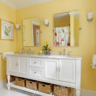 Immagine di una stanza da bagno country con lavabo a consolle, consolle stile comò, ante bianche, top in marmo, vasca ad alcova, vasca/doccia, WC a due pezzi, piastrelle bianche, piastrelle in pietra, pareti gialle e pavimento in marmo