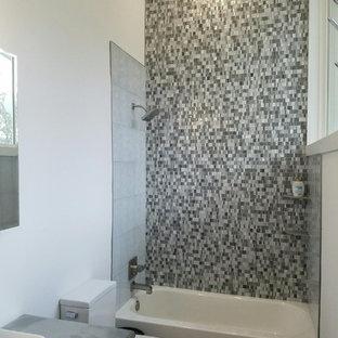 Immagine di una piccola stanza da bagno design con vasca da incasso, vasca/doccia, WC a due pezzi, piastrelle multicolore, piastrelle a mosaico, pareti bianche, lavabo a bacinella e top in acciaio inossidabile