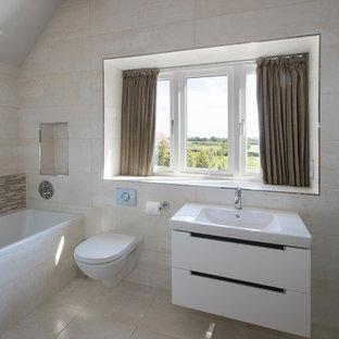 Exemple d'une salle de bain tendance pour enfant avec une baignoire posée, une douche à l'italienne, du carrelage en pierre calcaire, un mur beige, un sol en calcaire, un plan de toilette en terrazzo et aucune cabine.