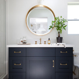 Exemple d'une salle de bain bord de mer de taille moyenne avec des portes de placard noires, un plan de toilette en marbre, un carrelage multicolore, un mur blanc, un plan vasque et un placard à porte shaker.
