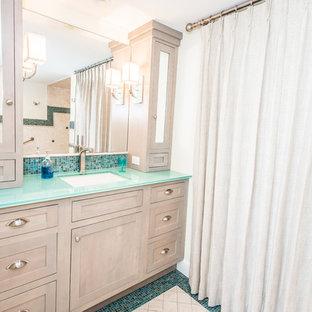 Foto på ett stort maritimt en-suite badrum, med skåp i shakerstil, skåp i ljust trä, ett badkar i en alkov, en dusch i en alkov, en toalettstol med separat cisternkåpa, blå kakel, mosaik, beige väggar, mosaikgolv, ett undermonterad handfat, bänkskiva i glas och dusch med duschdraperi