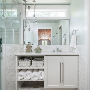 アトランタの小さいビーチスタイルのおしゃれな浴室 (シェーカースタイル扉のキャビネット、白いキャビネット、白いタイル、緑の壁、アンダーカウンター洗面器、ベージュの床、白い洗面カウンター) の写真
