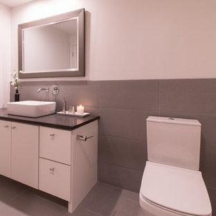 Immagine di una stanza da bagno padronale moderna di medie dimensioni con ante lisce, ante bianche, vasca ad alcova, doccia alcova, WC a due pezzi, piastrelle grigie, pareti bianche, lavabo a bacinella e top in quarzo composito