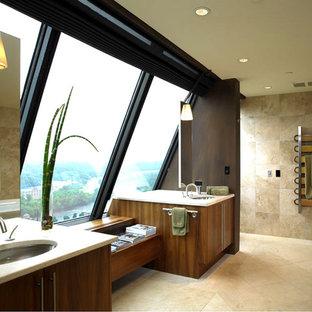 Cette photo montre une grand salle de bain principale tendance avec un placard à porte plane, des portes de placard en bois brun, une baignoire posée, des carreaux de miroir, un mur beige, un sol en carrelage de céramique, un lavabo encastré et un plan de toilette en stéatite.