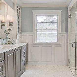 Klassisk inredning av ett stort vit vitt badrum för barn, med luckor med upphöjd panel, grå skåp, en kantlös dusch, en toalettstol med separat cisternkåpa, vit kakel, porslinskakel, blå väggar, marmorgolv, ett undermonterad handfat, bänkskiva i kvarts, vitt golv och dusch med gångjärnsdörr